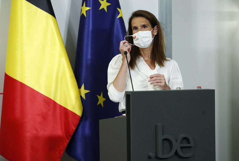 Belgium's Prime Minister Sophie Wilmes removes her face mask during a news conference following a meeting of the National Security Council amid the coronavirus outbreak in Brussels, Monday, July 27, 2020. Belgian Prime Minister Sophie Wilmes unveiled Monday a new set of drastic social distancing measures aimed at avoiding a new general lockdown amid a surge of COVID-19 infections. (Francois Lenoir, Pool Photo via AP)