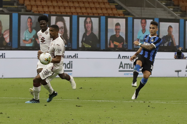 Inter Milan's Lautaro Martinez, right, scores his side's third goal during a Serie A soccer match between Inter Milan and Torino, at the San Siro stadium in Milan, Italy, Monday, July 13, 2020. (AP Photo/Luca Bruno