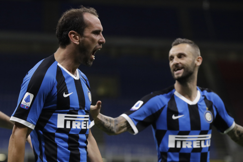 Inter Milan's Diego Godin, left, celebrates after scoring his side's second goal during a Serie A soccer match between Inter Milan and Torino, at the San Siro stadium in Milan, Italy, Monday, July 13, 2020. (AP Photo/Luca Bruno