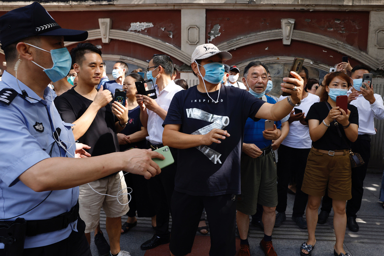A police man urges residents taking photos outside the United States Consulate to move on in Chengdu in southwest China's Sichuan province on Sunday, July 26, 2020. China ordered the United States on Friday to close its consulate in the western city of Chengdu, ratcheting up a diplomatic conflict at a time when relations have sunk to their lowest level in decades. (AP Photo/Ng Han Guan)