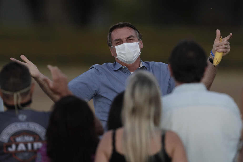 Brazil's President Jair Bolsonaro, who was infected with COVID-19, wore a protective face mask as he talks with supporters during a Brazilian flag retreat ceremony outside his official residence the Alvorada Palace, in Brasilia, Brazil, Friday, July 24, 2020. Bolsonaro now says he has tested negative though he tested positive for the new coronavirus for the third time, following his July 7 announcement that he had COVID-19, the Brazilian government confirmed. (AP Photo/Eraldo Peres)