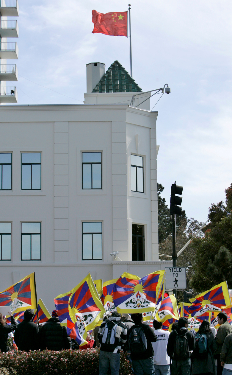 FILE – In this April 8, 2008 file photo, Tibetans and supporters waves Tibetan flags at a rally in protest of China's Olympic torch at the Chinese Consulate in San Francisco.  The Chinese consulate in San Francisco is harboring a Chinese researcher who the FBI says lied about her military background. (AP Photo/Jeff Chiu)