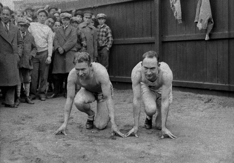 """FILE – In this March 29, 1928, file photo, American sprinters and Olympic champions Jackson Scholz, left, and Charles """"Charley"""" Paddock pose together in their starting positions at New York's Columbia University. (AP Photo/File)"""