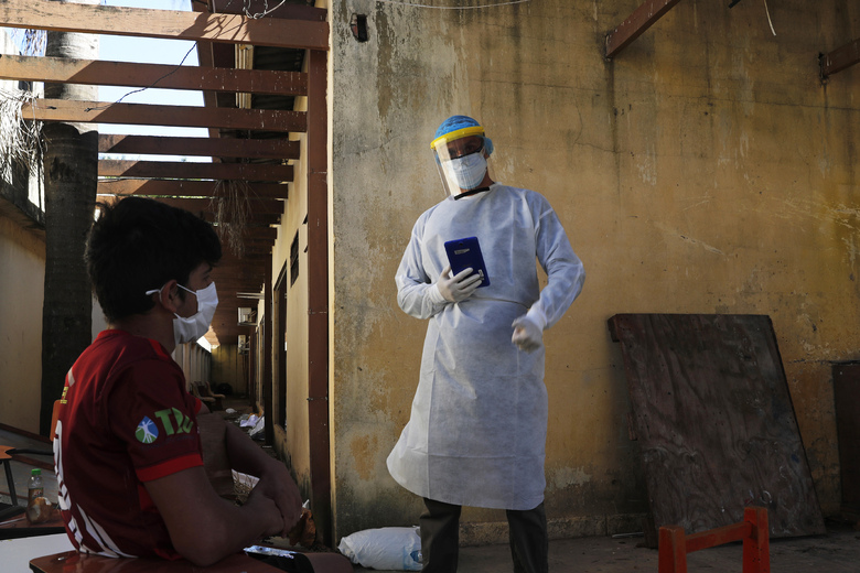 A youth in quarantine is interviewed by a member of the National Mechanism to Prevent Torture (MNPT) at a school being used as a government-run shelter where citizens returning home are required by law to quarantine for two weeks and pass two consecutive COVID-19 tests, as a preventive measure amid the COVID-19 pandemic in Ciudad del Este, Paraguay, Thursday, June 24, 2020. The youth said he'd been there for two months. While Paraguay appears to be controlling the disease, it faces concerns about a predicted 5% drop in gross domestic product for an economy that was already struggling, and a health system that remains unprepared for a large-scale epidemic. (AP Photo/Jorge Saenz)