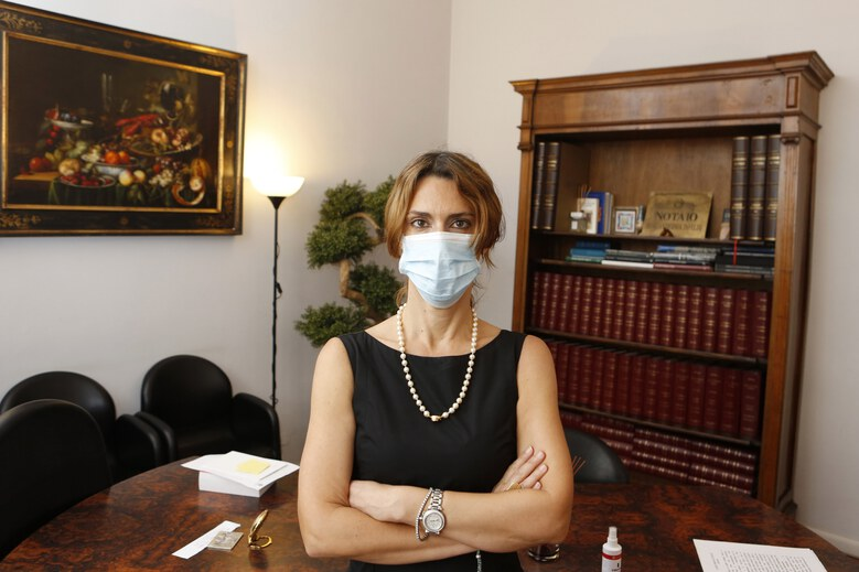 """Notary Ilaria Virginia Infelisi poses with a surgical mask in her studio in Rome, Tuesday, July 21, 2020. """"In my study, I'm very unpermissive. I ask everyone to wear it during the drafting of contracts even if there is a lot of space and everything is disinfected after each meeting. We ask it politely because I believe it is fundamentally a sign of courtesy and mutual respect"""". (AP Photo/Riccardo De Luca)"""