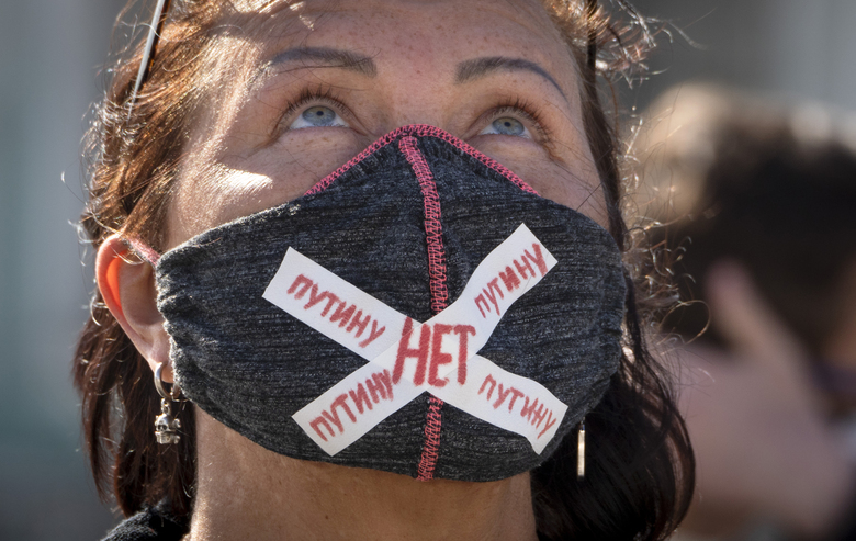 "A woman wears a face mask to protect against coronavirus infection with a sign ""No to Putin"" during a protest against constitutional amendments at the Palace Square in St.Petersburg, Russia, Wednesday, July 1, 2020. The vote on the constitutional amendments that would reset the clock on Russian President Vladimir Putin's tenure and enable him to serve two more six-year terms is set to wrap up Wednesday. (AP Photo/Dmitri Lovetsky)"