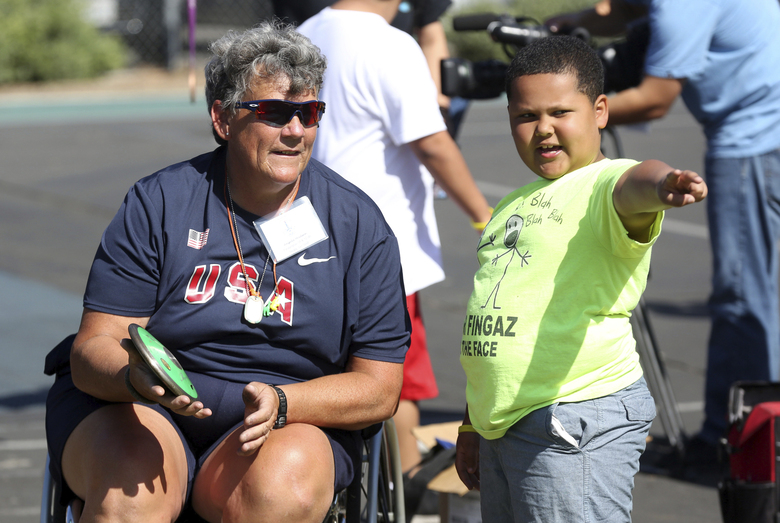 FILE – In this May 2, 2015, file photo, Paralympian Angela Madsen, left, works with Los Angeles Unified School District students during Ready, Set, Gold! Day at Trinity Street Elementary in Los Angeles. A three-person crew left the Hawaii Yacht Club Wednesday, July 29, 2020, to search for the craft piloted by Angela Madsen, who died in the Pacific Ocean last month, The Honolulu Star-Advertiser reported Thursday. (Photo by Matt Sayles/Invision for Samsung/AP Images, File)