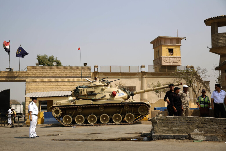 "FILE – In this Aug. 2, 2015 file photo, Egyptian security forces stand guard outside one of the entrances of Tora prison, in Cairo, Egypt. Since the coronavirus first hit Egypt in February 2020, At least 10 doctors and six journalists have been arrested according to rights groups. Other health workers say they have been warned by administrators to keep quiet or face punishment. One foreign correspondent has fled the country, fearing arrest, and another two have been summoned for reprimand over their reporting of ""disinformation"" and other ""violations."" (AP Photo/Hassan Ammar, File)"