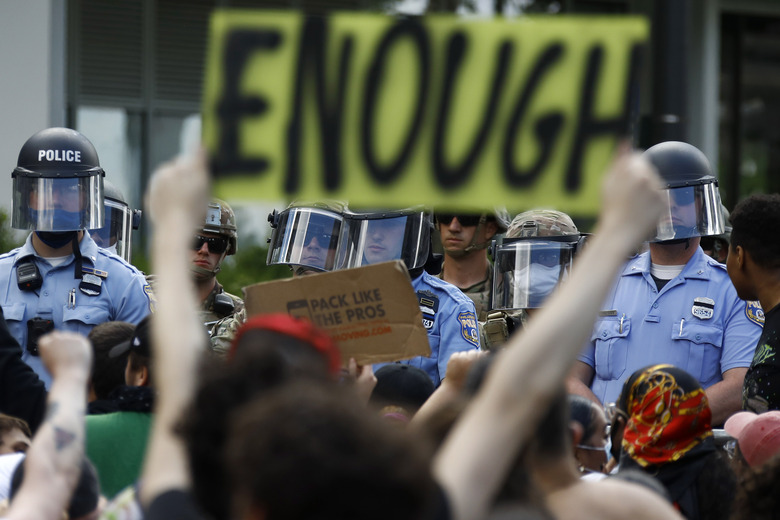 FILE – In this June 1, 2020, file photo, protesters rally as Philadelphia Police officers and Pennsylvania National Guard soldiers look on in Philadelphia, over the death of George Floyd, a black man who was in police custody in Minneapolis. (AP Photo/Matt Slocum, File)
