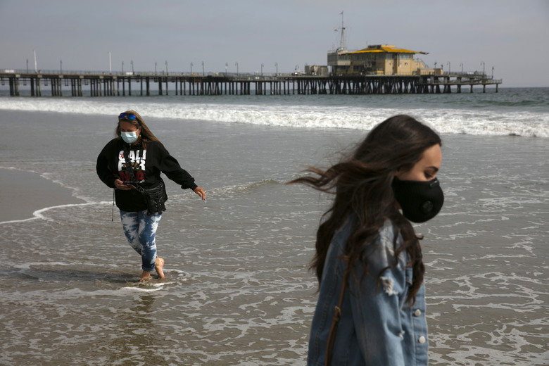 FILE – In this June 23, 2020, file photo, Malia Pena, foreground, and her mother, Lisa Torriente, wear masks as they visit the beach in Santa Monica, Calif. (AP Photo/Jae C. Hong, File)