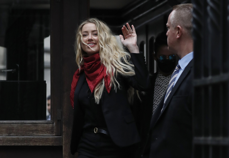 """Actress Amber Heard, center, arrives at the High Court in London, Thursday, July 16, 2020. Actor Johnny Depp is suing News Group Newspapers, publisher of The Sun, and the paper's executive editor, Dan Wootton, over an April 2018 article that called him a """"wife-beater."""" The Sun's defense relies on a total of 14 allegations by Heard of Depp's violence. He strongly denies all of them.  (AP Photo/Alastair Grant)"""
