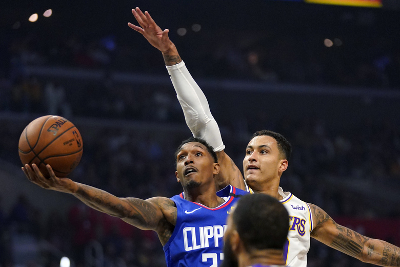 FILE – In this March 8, 2020, file photo, Los Angeles Clippers guard Lou Williams, left, shoots as Los Angeles Lakers forward Kyle Kuzma defends during the first half of an NBA basketball game in Los Angeles. (AP Photo/Mark J. Terrill, File)