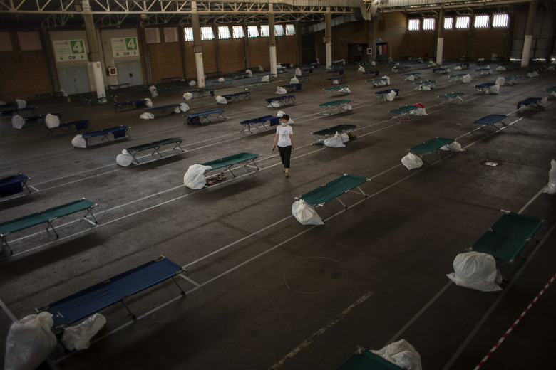 A local worker walks along an exhibition center turned into a temporary seasonal workers' shelter in Lleida, Spain, Thursday, July 2, 2020. Authorities in northeast Spain have ordered the lockdown of a county around the city of Lleida due to worrying outbreaks of the COVID-19 virus. Catalan regional authorities announced Saturday, July 4, 2020 that as of noon local time movement will be restricted to and from the county of El Segriá around Lleida which is home to over 200,000 people. Residents will have until 4 p.m. to enter the area. The new outbreaks are linked to agricultural workers in the rural area. (AP Photo/Emilio Morenatti)