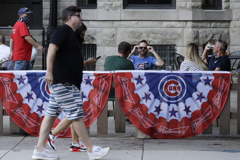 Chicago Cubs fans sit at Murphy's Bleachers bar outside Wrigley field before an opening day baseball game against the Milwaukee Brewers in Chicago, Friday, July 24, 2020, in Chicago. In a normal year, that would mean a sellout crowd at Wrigley Field and jammed bars surrounding the famed ballpark but in a pandemic-shortened season, it figures to be a different atmosphere. (AP Photo/Nam Y. Huh)