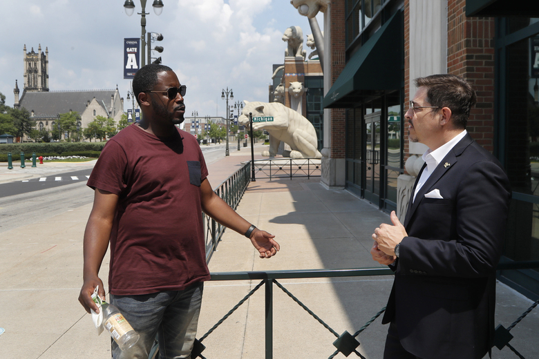 "Kenny Valentino, left, manager of Delmar, a rooftop business in Greektown, and Adrian Tonon, the 24-Hour Economy Ambassador for Detroit Mayor Mike Duggan, talk, Wednesday, July 8, 2020, in Detroit. Bars and restaurants in the area are desperately hoping people come watch games in nearly empty ballparks on TV in establishments as packed as possible with social distancing guidelines. ""The real fans will still want to come out and be around other fans and not just watch the games at home,"" Valentino said. (AP Photo/Carlos Osorio)"