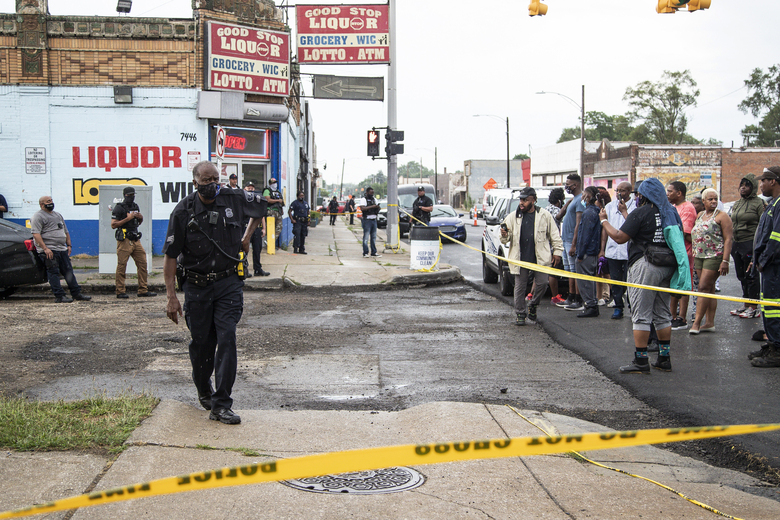 Residents in the area confront Detroit Police officers following the fatal shooting of a man, Friday, July 10, 2020, who the city's police chief said fired at officers investigating a Fourth of July block party shooting, in Detroit. (Junfu Han/Detroit Free Press via AP)