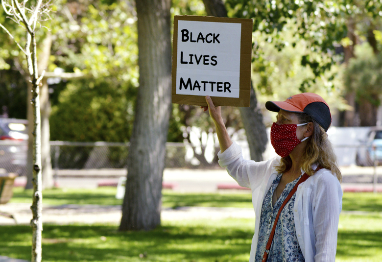 A demonstrator holds a Black Lives Matter sign during a protest on Thursday, July 30, 2020, in Albuquerque, N.M., denouncing President Donald Trump's decision to send federal agents to the city to fight crime. Peace activists in Albuquerque said they are preparing to greet the new federal agents coming New Mexico's largest city, where police and protesters have clashed in recent years over police shootings. (AP Photo/Russell Contreras)