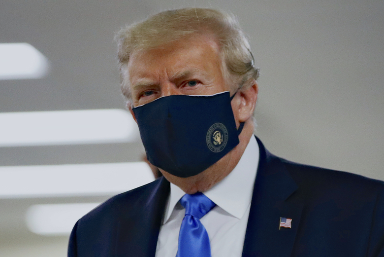 President Donald Trump wears a face mask Saturday, July 11, 2020, during a visit to Walter Reed National Military Medical Center in Bethesda, Md. When he wore a mask publicly for the first time, he chose a navy-blue one that bore the presidential seal. It also matched the color of his suit. (AP Photo / Patrick Semansky