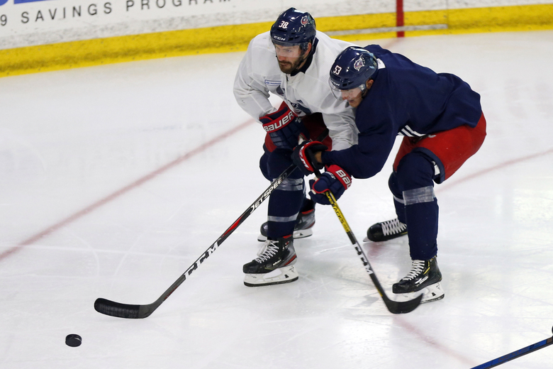 Columbus Blue Jackets' Boone Jenner, left, and Gabriel Carlsson, of Sweden, chase a loose puck during NHL hockey practice, Friday, July 24, 2020, in Columbus, Ohio. (AP Photo/Jay LaPrete)