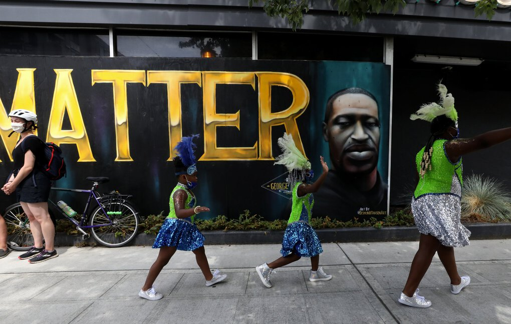 The Washington Diamonds Drill Team & Drumline pass a depiction of George Floyd on a Black Lives Matter mural at 23rd Avenue and Union on Saturday. (Alan Berner / The Seattle Times)