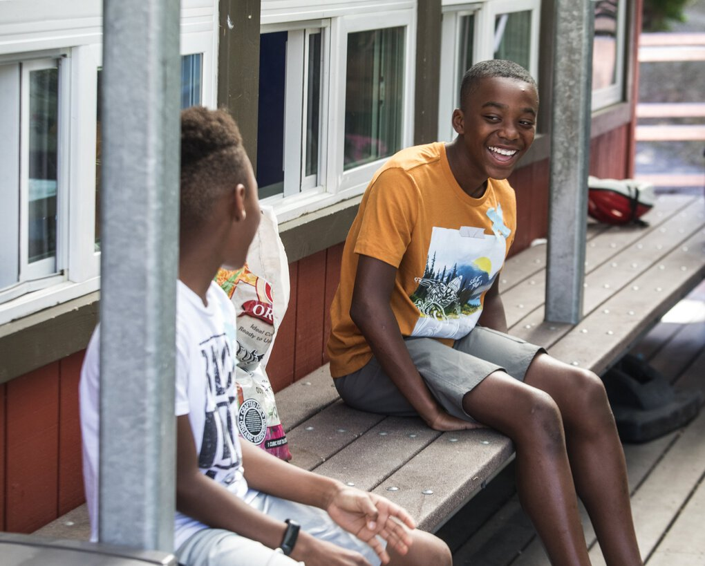 Student Xavier Landry, 12, right, talks with Andre Turner, 7, while still keeping social distance during outdoor play time at Tiny Tots Development Center.   (Steve Ringman / The Seattle Times)