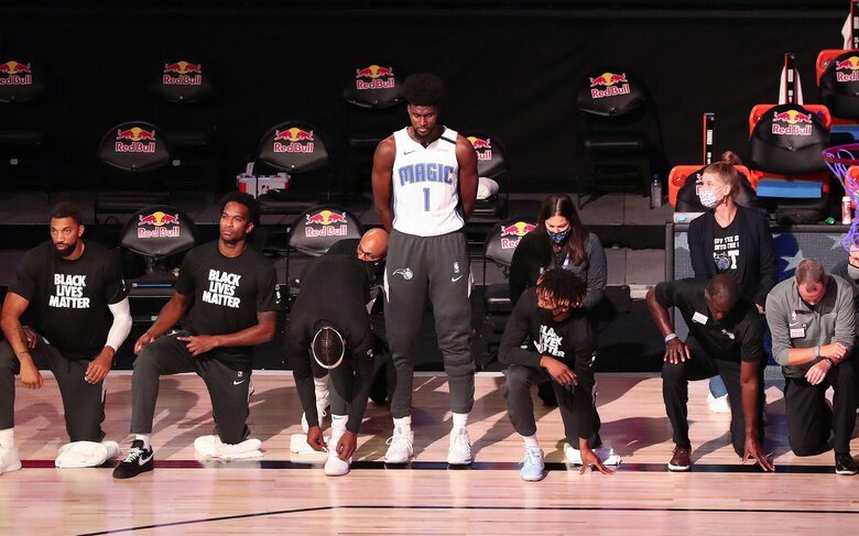 Orlando Magic forward Jonathan Isaac (1) is the lone player to stand and not wear a Black Lives Matter T-shirt before a game July 31 against the Brooklyn Nets in Lake Buena Vista, Florida. (Charles King / Orlando Sentinel/TNS)
