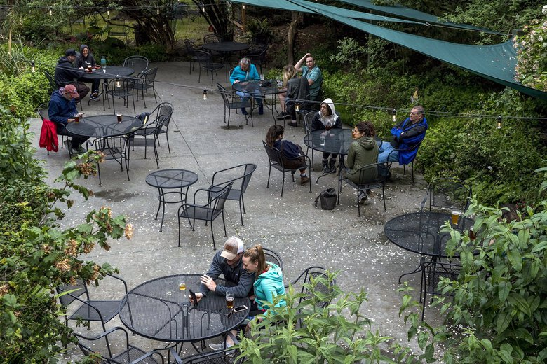 Visitors enjoy beer and food at Walking Man Brewing in Stevenson, Washington this summer. The new Dietary Guidelines for Americans reduced alcohol intake limits for men from two drinks per day, which was already recommended for women. (Amanda Snyder / The Seattle Times)