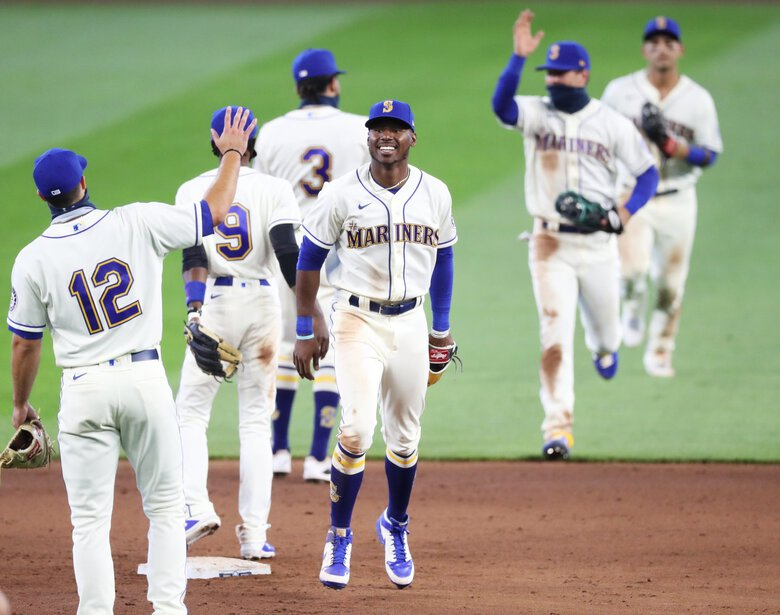 The Mariners, Kyle Lewis at center, celebrate a win over the Rockies 5-3 on Sunday. (Ken Lambert / The Seattle Times)