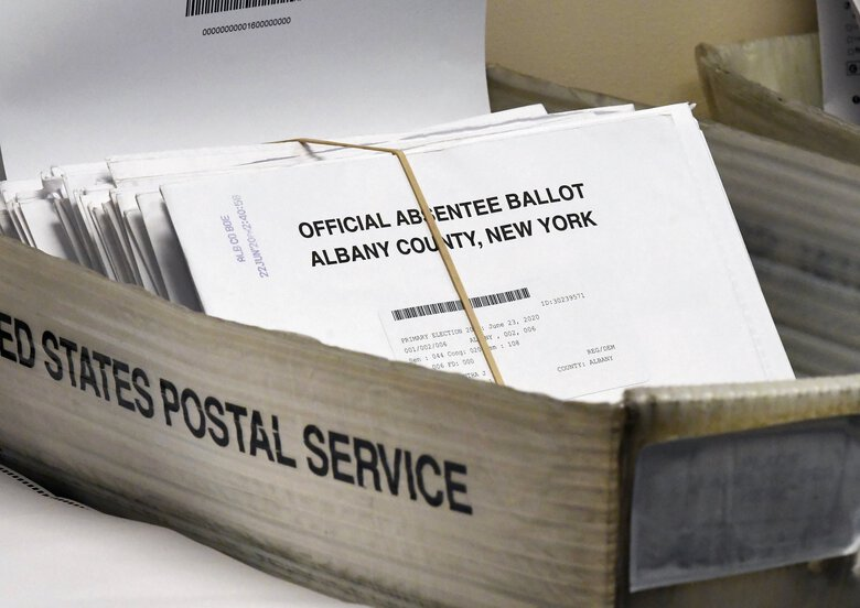 "A box of absentee ballots wait to be counted at the Albany County Board of Elections in Albany, N.Y. Though the terms vary from state-to-state, as do the laws, the terms ""absentee voting,"" ""mail-in voting"" and even ""universal vote by mail"" have different meanings than the ones Trump has assigned to them, causing some confusion about the November election. (Hans Pennink / The Associated Press)"