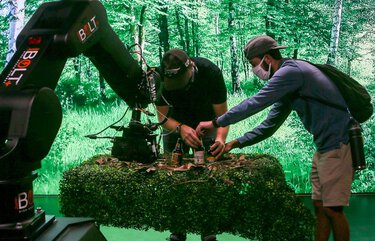 Max Deroin, a motion control operator, and Nick Morales, an assistant cameraman and operator, make adjustments to the set while practicing operating new equipment. The robot will help replace on-set crew as the studio makes efforts to create a safe space for filming amid the COVID-19 pandemic.
