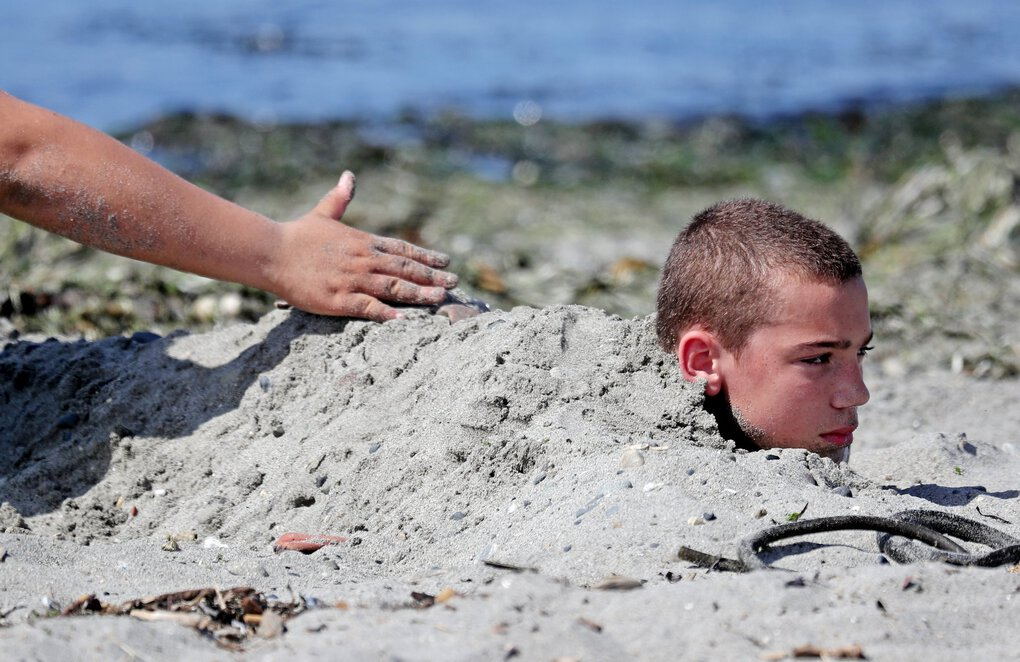 At Brackett's Landing in Edmonds, Jayden King, 13, keeps cool under a few inches of sand applied by his cousin, as temperatures hit the 90s Sunday. (Ken Lambert / The Seattle Times)