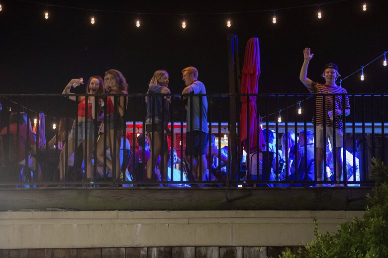 Patrons stand on the Bear Trap's rooftop bar on the Strip, the University of Alabama's bar scene, on Saturday in Tuscaloosa, Ala. (Vasha Hunt / Associated Press)