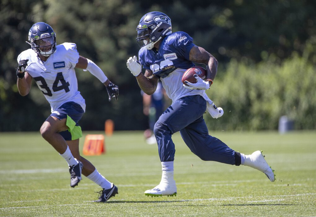 Running back Chris Carson during practice Monday, defended by Linden Stephens (34).  The Seattle Seahawks practice at the VMAC in Renton, WA, Monday August 17, 2020. (Dean Rutz / The Seattle Times)