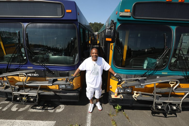 Bus driver Stanley Bascomb, a 32-year Metro veteran, opted to pose with two newer bus models at the Metro Employees Historic Vehicle Association vintage bus yard. (Ken Lambert / The Seattle Times)