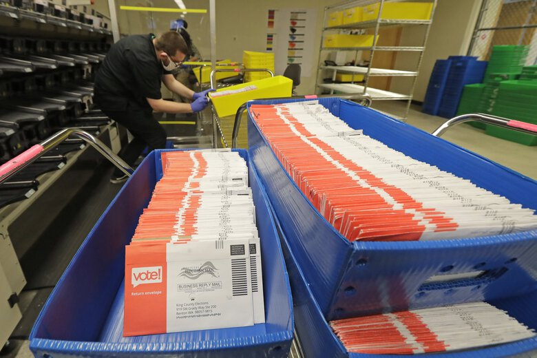In this Aug. 5 file photo, mailed ballots are shown in sorting trays at the King County Elections headquarters in Renton. On Tuesday, Washington state Attorney General Bob Ferguson filed a lawsuit against the Trump administration over recent changes to the U.S. Postal Service that Ferguson says has slowed mail delivery. (Ted S. Warren / The Associated Press)