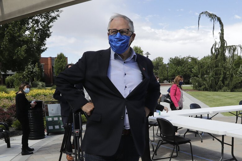 """Gov. Jay Inslee, shown here in Yakima in June, said in a news conference Thursday he was """"cautiously pleased"""" at the state's progress in tamping down the coronavirus outbreak. (Elaine Thompson / The Associated Press)"""