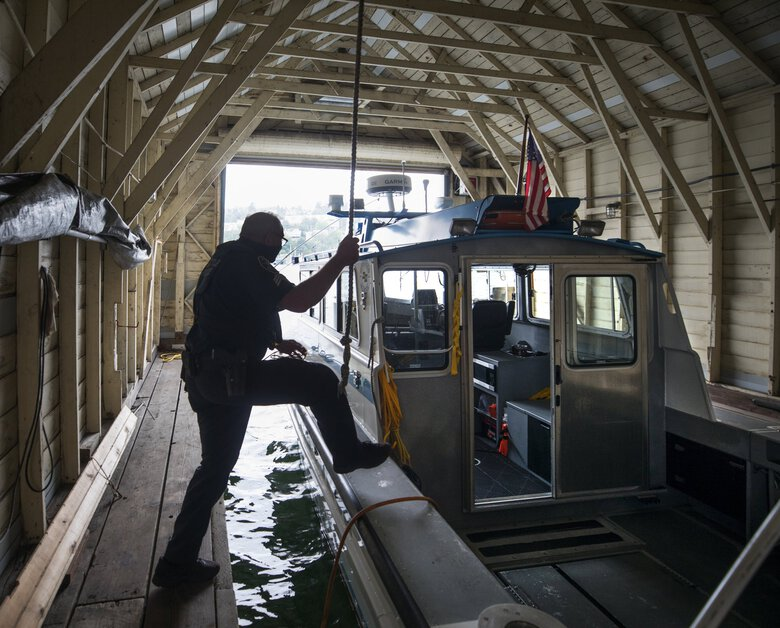 Sgt. Kevin Haistings of the Seattle Harbor Patrol steps aboard one of the police boats equipped with sonar.   (Steve Ringman / The Seattle Times)