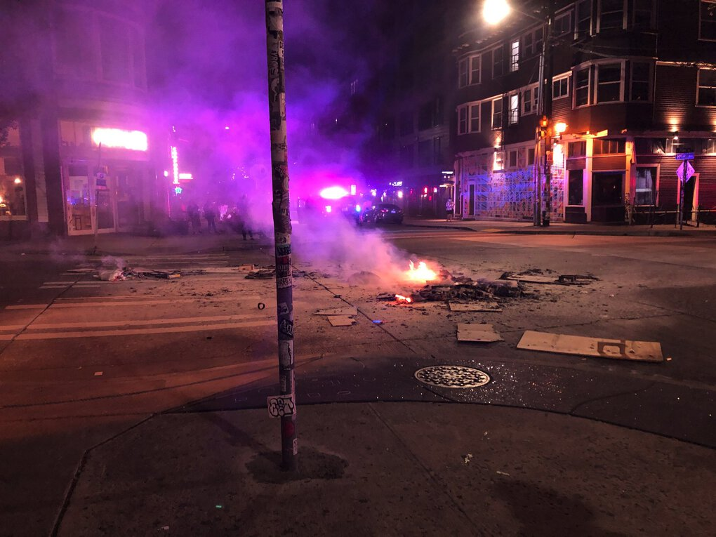 After police ordered protesters at the East Precinct to disperse, someone lit a fire on East Pike Street. (Heidi Groover / The Seattle Times)