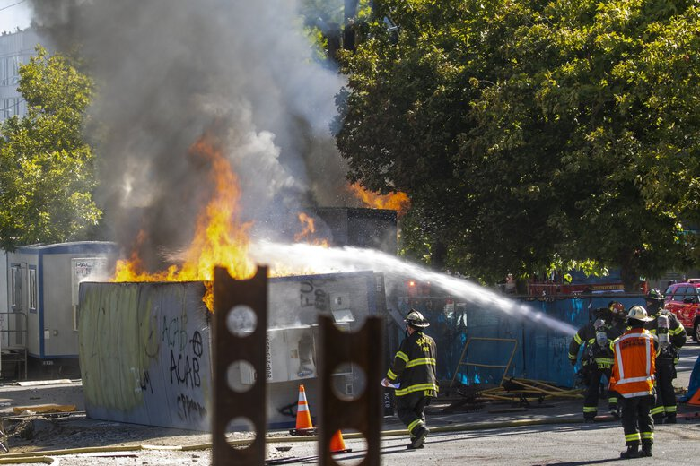 Seattle firefighters douse burning construction trailers at the new King County juvenile detention center on July 25. (Bettina Hansen / The Seattle Times)
