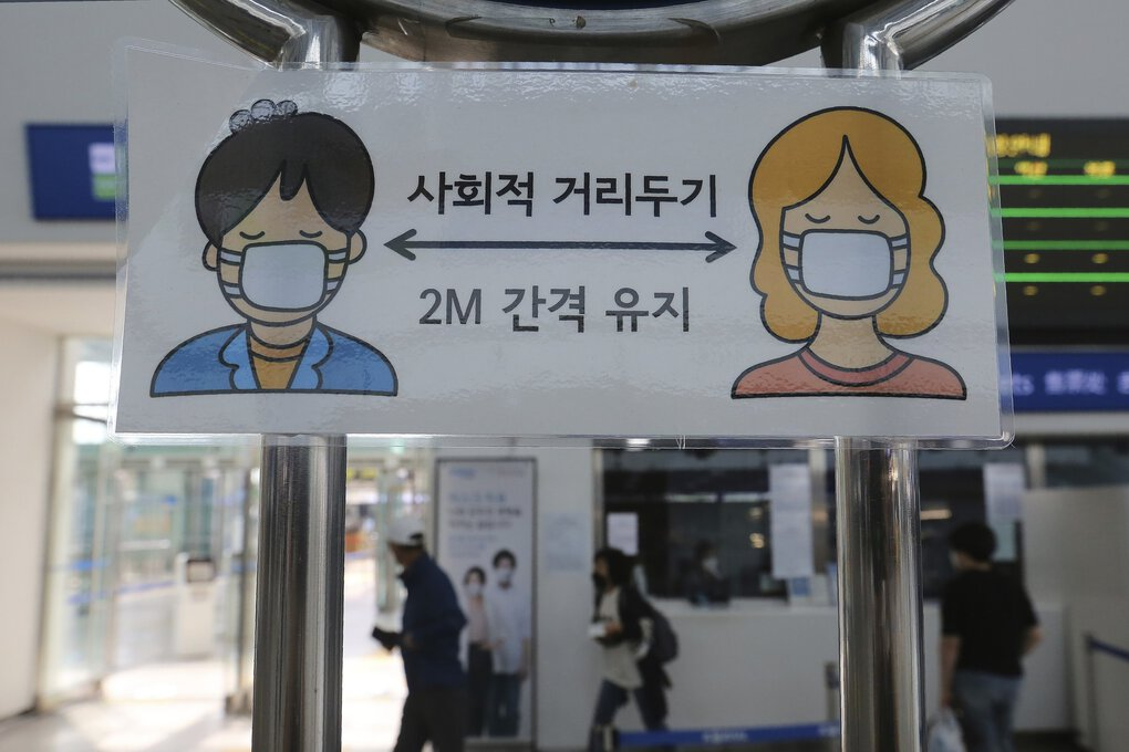 A sign encouraging social distancing is seen at the Seoul train station in South Korea on Tuesday South Korea will ban large public gatherings and shut down churches and nightspots in the greater capital area following an alarming surge in coronavirus cases. (Ahn Young-joon / The Associated Press)