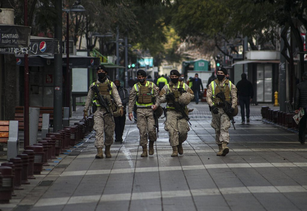 Soldiers patrol a pedestrian walkway in Santiago, Chile, to monitor the entry of any pedestrians in a city that has put very strict restrictions on movement. (Esteban Felix / The Associated Press)