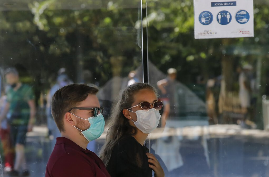 People wearing masks to prevent the spread of COVID-19, ride the little train at the Chateau de Versailles outside Paris.   (Michel Euler / The Associated Press)