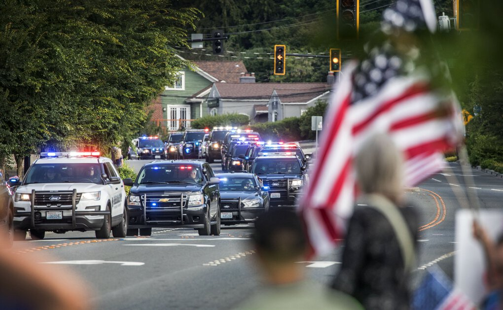 A procession of police and fire departments winds down Northeast Bothell Way on Tuesday in honor of Bothell Police Officer Jonathan Shoop, who was killed in the line of duty. Residents lined the street holding American flags, saluting, taking photos and remaining quiet during the procession.  (Steve Ringman / The Seattle Times)