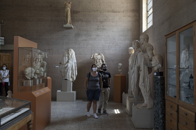 Tourists wearing protective face masks among exhibits inside the Museum of Ancient Corinth, Greece, on Aug. 1, 2020. (Bloomberg photo by Konstantinos Tsakalidis).