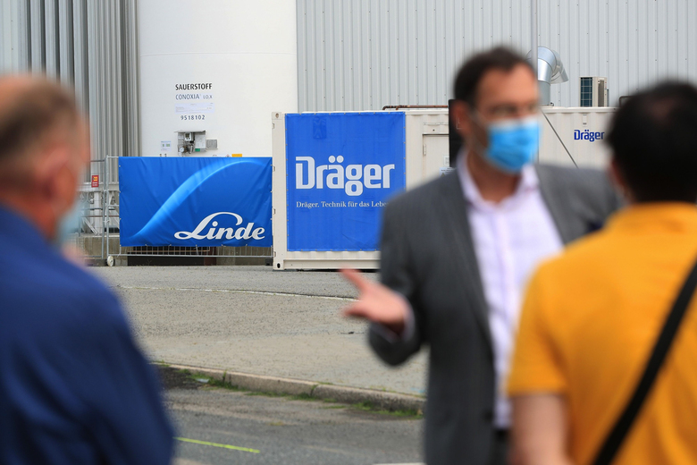Attendees wear protective face masks near Linde and a Draegerwerk logos on banners outside the Jaffestrasse Corona Treatment Center at the Berlin Messe exhibition space in Berlin on Aug. 14, 2020. (Bloomberg photo by Krisztian Bocsi).