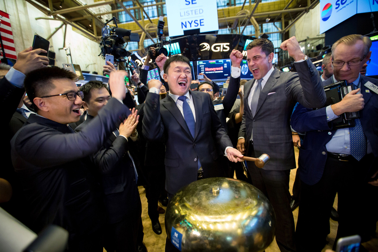 Forrest Li, chairman, chief executive officer and co-founder of Sea Ltd. (center) rings a ceremonial bell during the company's initial public offering on the floor of the New York Stock Exchange in New York on Oct. 20, 2017. (Bloomberg photo by Michael Nagle).