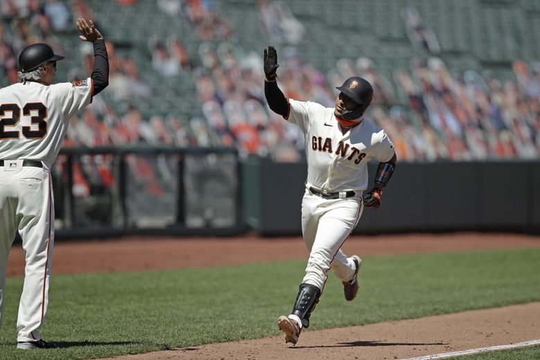 San Francisco Giants' Chadwick Tromp, right, waves at third base coach Ron Wotus (23) after hitting a two run home run against the Texas Rangers in the sixth inning of a baseball game Sunday, Aug. 2, 2020, in San Francisco. (AP Photo/Ben Margot)