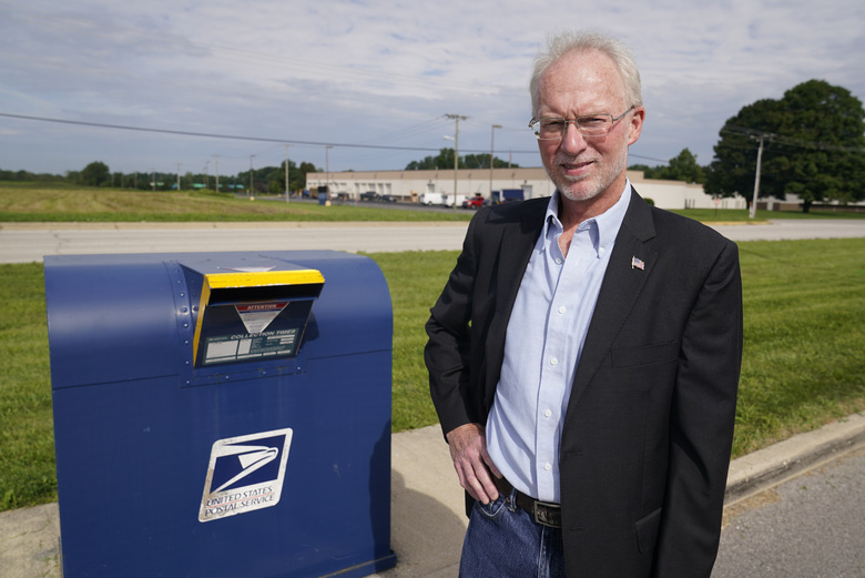 Doug Brown, postal staffer and president of the American Postal Workers Union chapter in Indiana, poses for a picture outside of a post office facility, Monday, Aug. 17, 2020, in Muncie, Ind. The U.S. Postal Service is expected to play a central role in this year's presidential elections with so many states promoting voting by mail amid the coronavirus pandemic. (AP Photo/Darron Cummings)