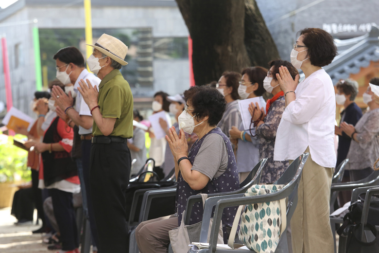 People wearing face masks to help protect against the spread of the coronavirus pray while maintaining social distancing during a service at the Chogyesa temple in Seoul, South Korea, Sunday, Aug. 23, 2020. (AP Photo/Ahn Young-joon)