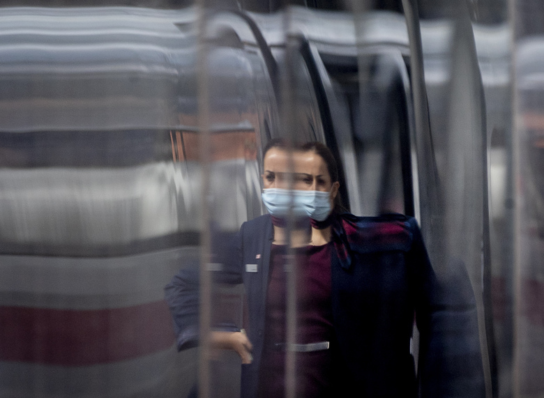 A conductor is reflected in a parked ICE train in the main train station in Frankfurt, Germany, Thursday, Aug. 27, 2020. . (AP Photo/MichMost of Germany will impose a minimum fine of 50 euros ($59) for breaching mask-wearing rules as coronavirus infections rise againael Probst)
